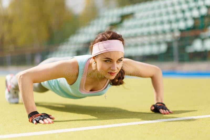 Jonge sportieve vrouw die duw op oefening in openlucht doen royalty-vrije stock afbeeldingen
