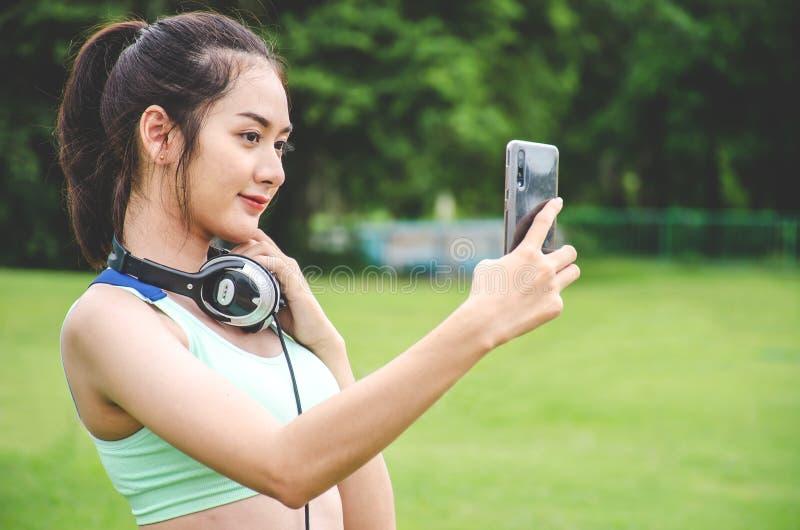 Jonge Sportieve Vrouw die een Selfie nemen bij Park Zij bekijkt Slimme Telefoon stock afbeelding