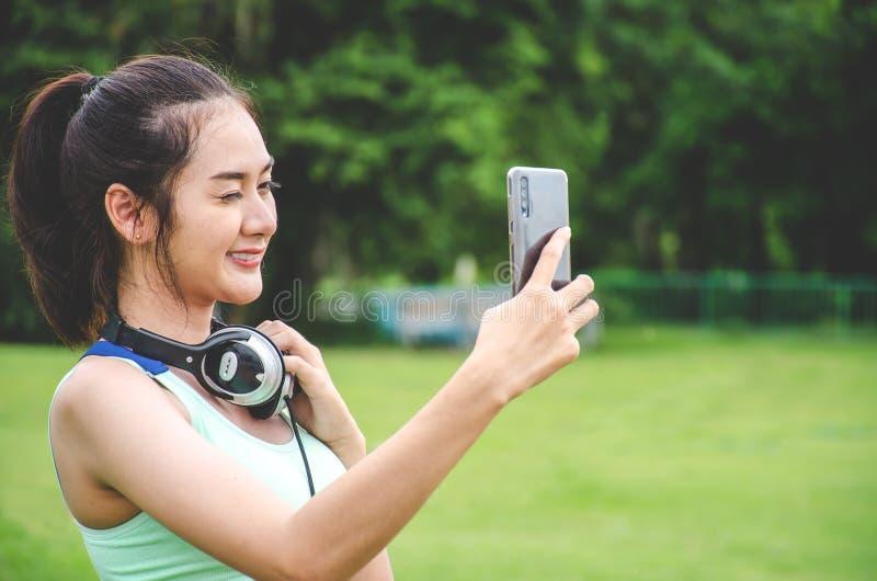 Jonge Sportieve Vrouw die een Selfie nemen bij Park Zij bekijkt Smartphone, heeft zij een Smartphonehouder op haar Wapen en luist stock foto's