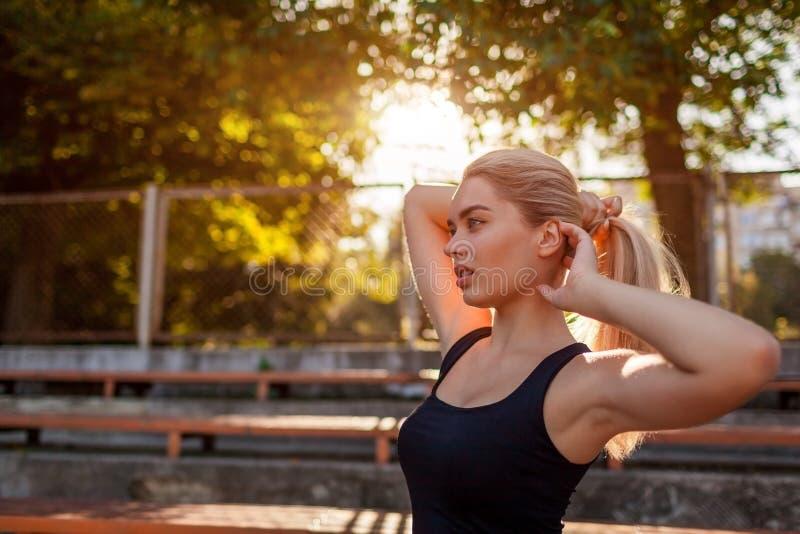 Jonge sportieve vrouw die haar haar binden in poneystaart op sportsground in de zomer Voorbereiding voor training royalty-vrije stock foto