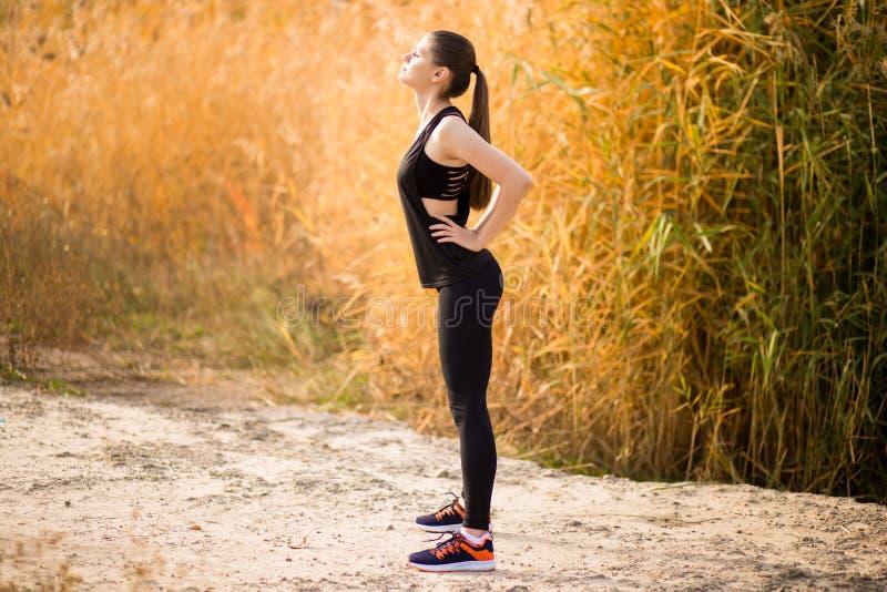 Jonge sportieve vrouw die oefeningen in de herfst doen Sportvrouw die haar lichaam uitrekken royalty-vrije stock foto