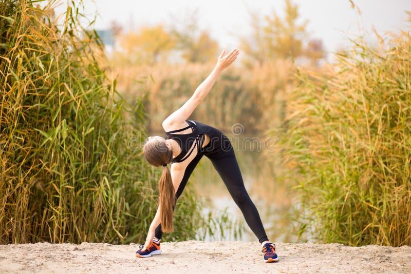 Jonge sportieve vrouw die oefeningen in de herfst doen Sportvrouw die haar lichaam uitrekken stock afbeeldingen