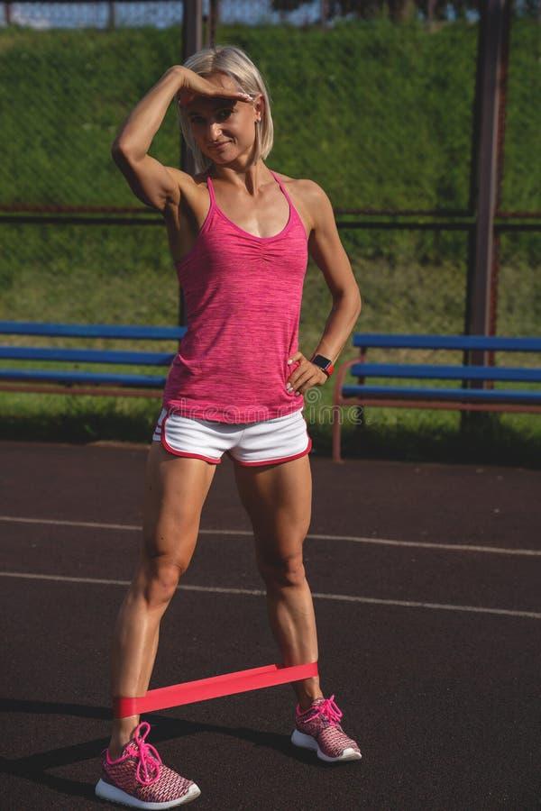 Jonge sportieve vrouw die oefeningen met elastiekje doen openlucht royalty-vrije stock foto