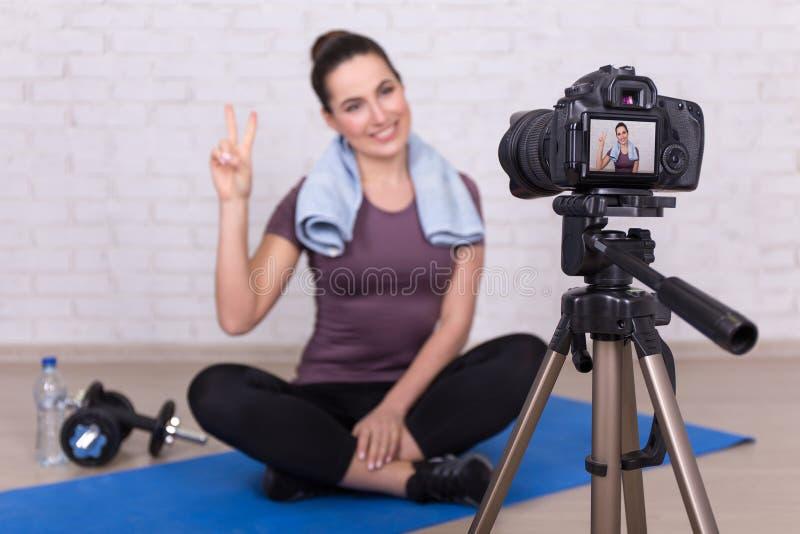 Jonge sportieve vrouw die vlogger nieuwe video thuis maken stock foto's