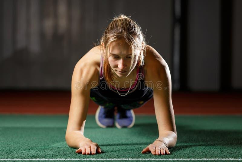 Jonge sportieve vrouw die zich in plank opleidingskern bevinden stock afbeeldingen