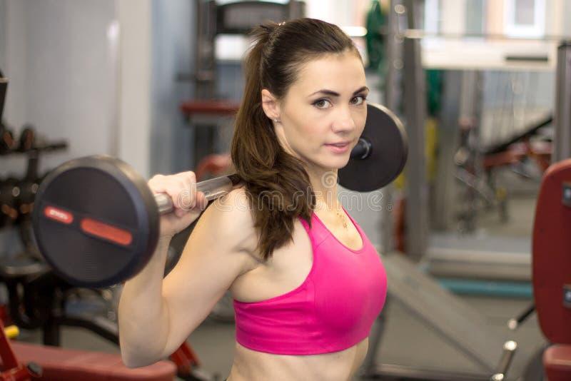Jonge sportieve vrouw het opheffen gewichten die in een gymnastiek uitwerken stock fotografie