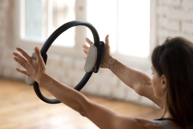 Jonge sportieve vrouw het praktizeren geschiktheidsoefening met pilates ri royalty-vrije stock foto's