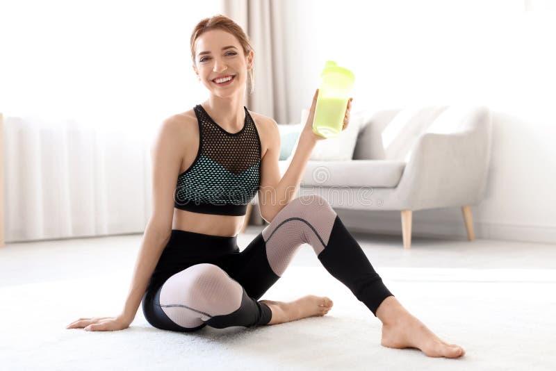 Jonge sportieve vrouw met fles van eiwitschokzitting op vloer thuis stock afbeeldingen