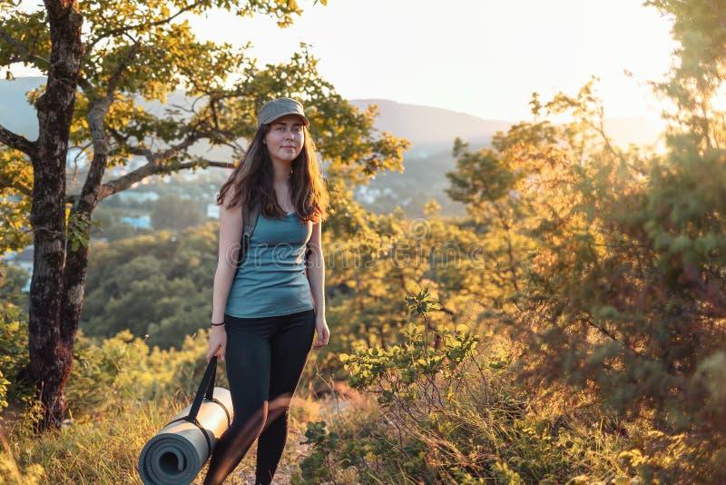 Jonge sportieve vrouw met yogamat in haar handen In de achtergrond, het bos en de zonsondergang Sporten, Fitness en gezond levens royalty-vrije stock foto