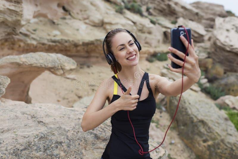 Jonge sportieve vrouwelijke bespreking op video in hoofdtelefoons terwijl het gebruiken van mobiele telefoon stock foto