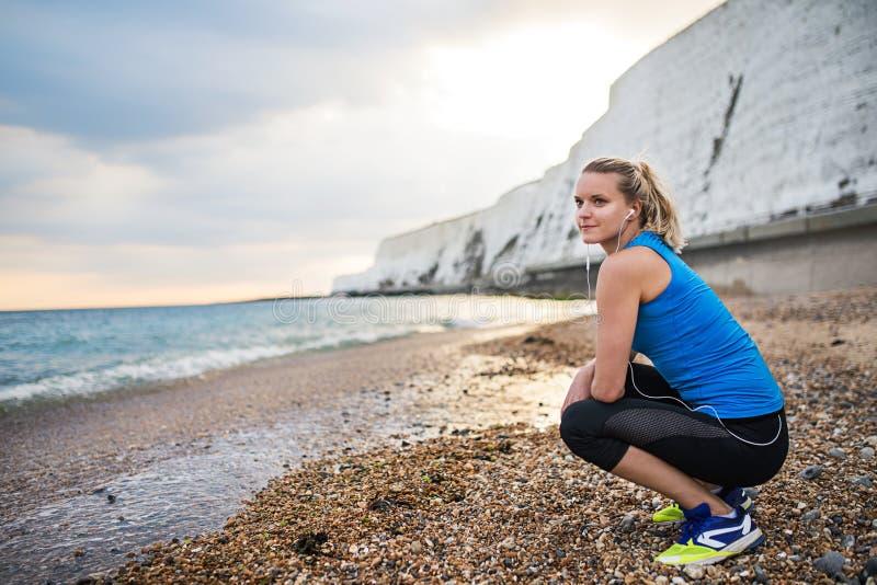 Jonge sportieve vrouwenagent met oortelefoons die op het strand buiten rusten stock fotografie