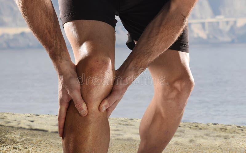 Jonge sportmens die met atletische benen knie in pijn houden die spierverwonding aan het lopen lijden stock foto's