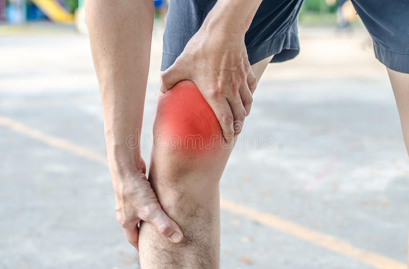 Jonge sportmens die met sterke atletische benen knie met van hem houden stock foto