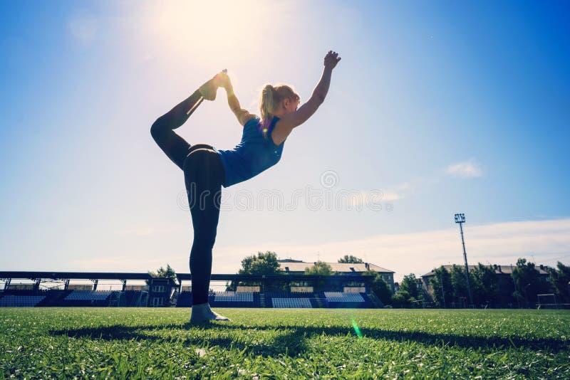 Jonge sportvrouw die de oefening doen die van het opwarmingssaldo zich op benen één bevinden die been en rug in openlucht uitrekk stock afbeelding