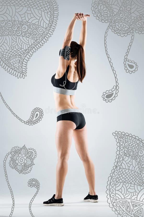 Jonge sportvrouw die haar lichaam uitrekken terwijl opleiding royalty-vrije stock afbeeldingen