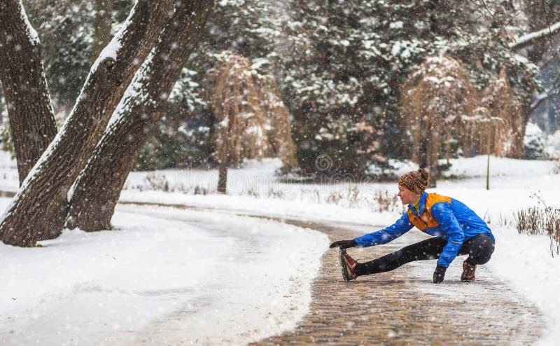 Jonge sportvrouw die oefeningen doen tijdens de winter opleiding buiten in koud sneeuwweer stock foto