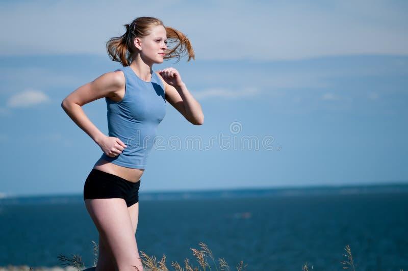 Jonge sportvrouw die op zonnige dag loopt stock fotografie