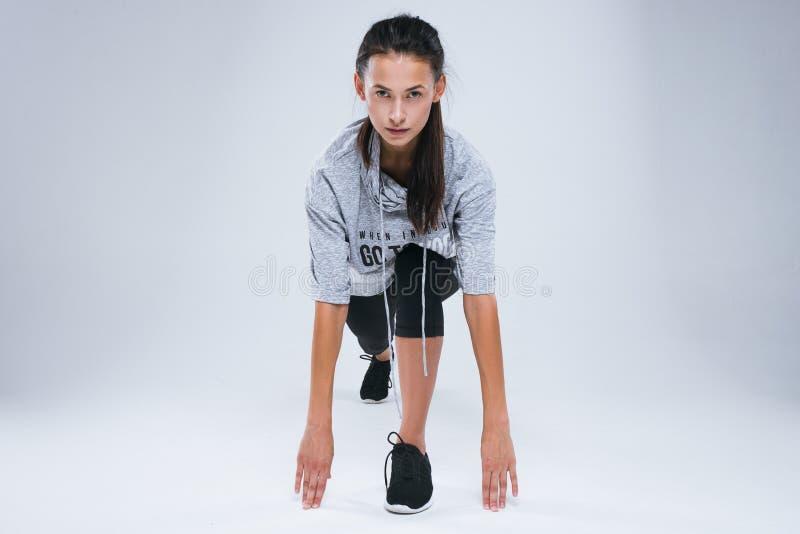Jonge sportvrouw die in sportslijtage over grijze achtergrond voorbereidingen treffen te lopen royalty-vrije stock foto
