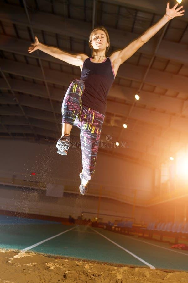Jonge sportvrouw die in vérspringenpoging vliegen royalty-vrije stock afbeelding