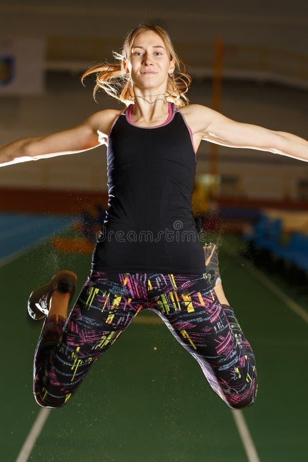 Jonge sportvrouw die in vérspringenpoging vliegen stock foto's