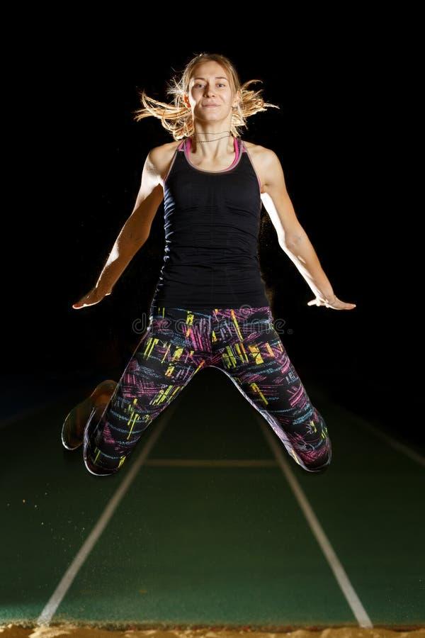 Jonge sportvrouw die in vérspringenpoging vliegen stock foto