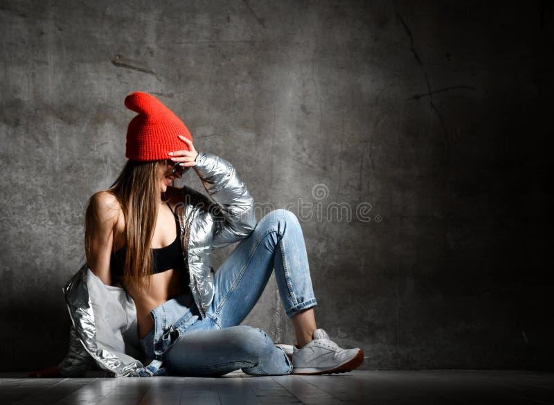 Jonge sportvrouw na trainingoefening stellen die in de zilveren sexy dunne benedenjeans van het kogelvisjasje lachen stock foto's