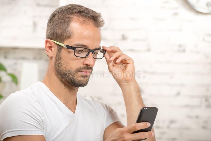 Jonge stafmedewerker die zijn cellphone kijken royalty-vrije stock foto's