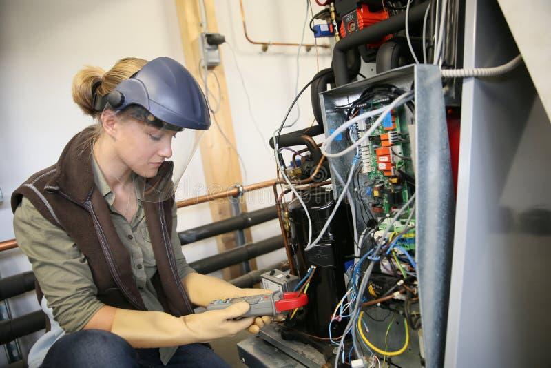 Jonge stagiair die elektronische installatie verifiëren stock fotografie