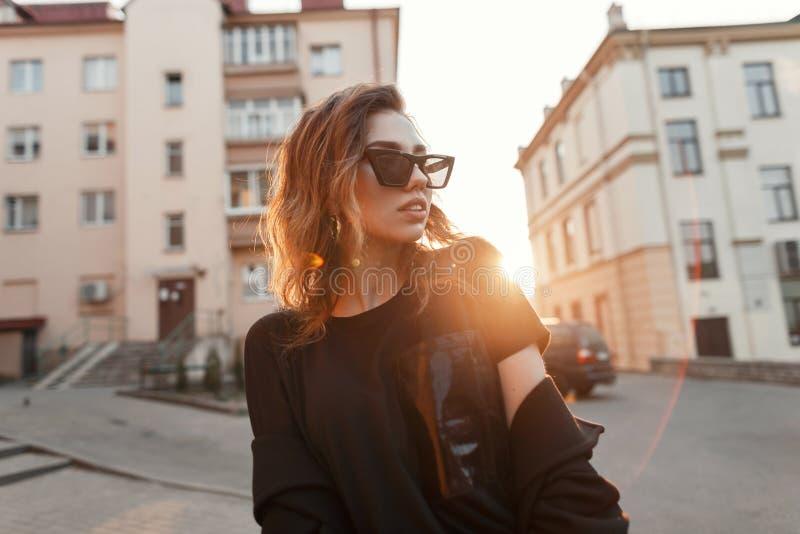Jonge stedelijke moderne hipstervrouw in zwarte modieuze T-shirt in donkere in zonnebril die op de straat dichtbij huizen in de s stock foto's