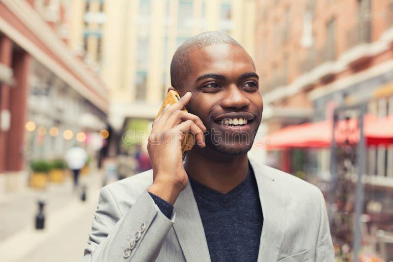 Jonge stedelijke professionele glimlachende mens die slimme telefoon met behulp van royalty-vrije stock foto's