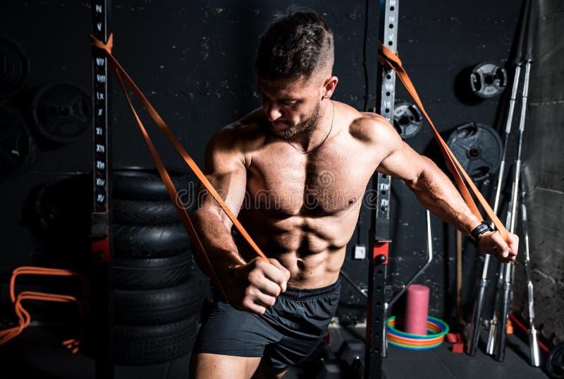 Jonge, sterk gefocusseerde, op spierkracht afgestemde borsthaald in geïmproviseerde gym met rubber voor kracht en goed uitziend s royalty-vrije stock afbeelding
