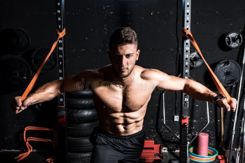 Jonge, sterk gefocusseerde, op spierkracht afgestemde borsthaald in geïmproviseerde gym met rubber voor kracht en goed uitziend s royalty-vrije stock afbeeldingen