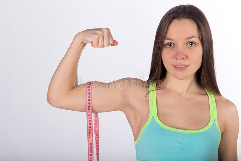 Jonge sterke de bicepsenspier van vrouwenmaatregelen stock foto's