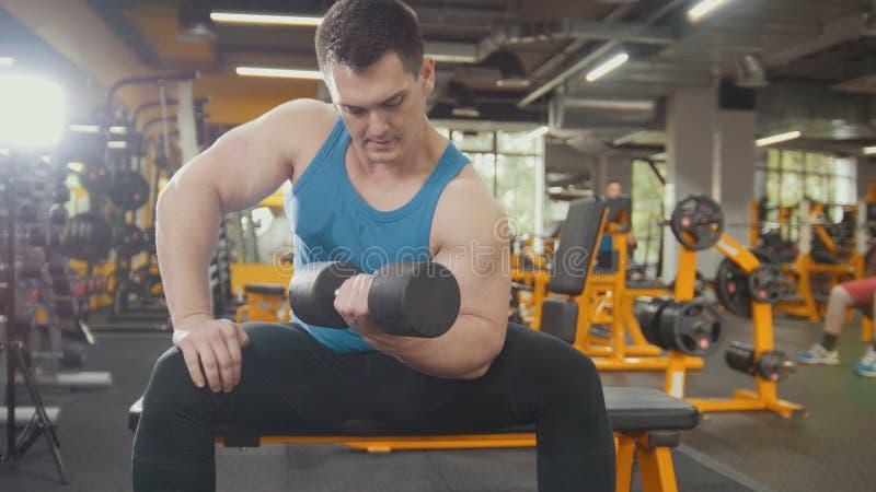 Jonge sterke mens die met domoren in de gymnastiek uitoefenen stock afbeelding