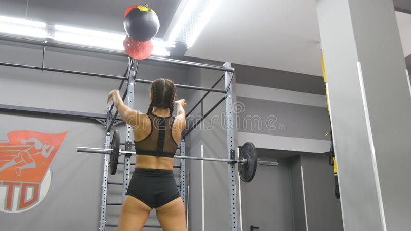 Jonge sterke vrouw met perfect geschiktheidslichaam in sportkleding die met geneeskundebal bij gymnastiek uitoefenen Meisje die c stock afbeelding