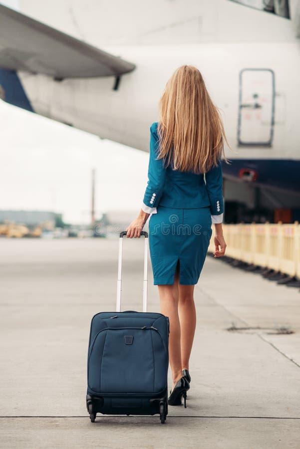 Jonge stewardess met koffer op vliegtuigenparkeren stock fotografie