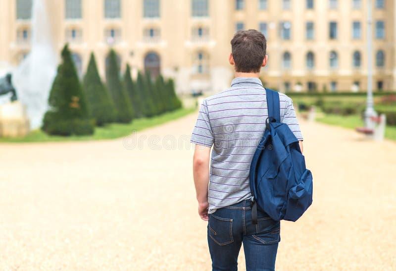 Jonge student die aan de universiteit lopen Achter mening stock foto's