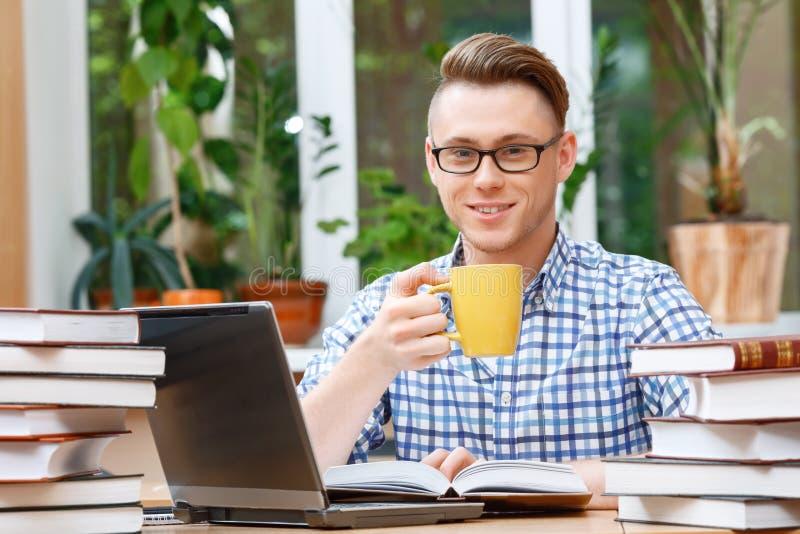 Jonge student die in een bibliotheek werken royalty-vrije stock afbeelding