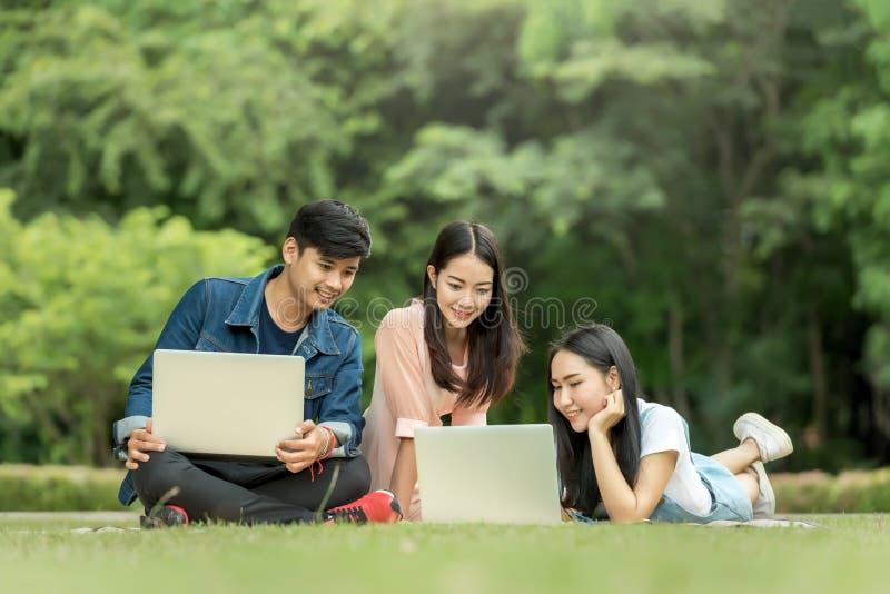 Jonge student die laptop samen in het park met behulp van stock fotografie