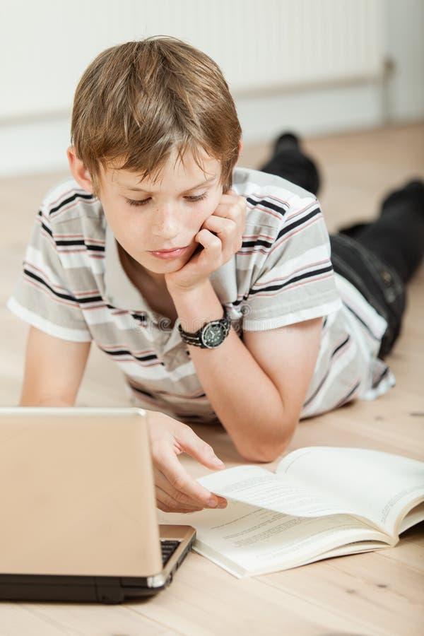 Jonge student die zijn schoolwork thuis doen stock afbeeldingen
