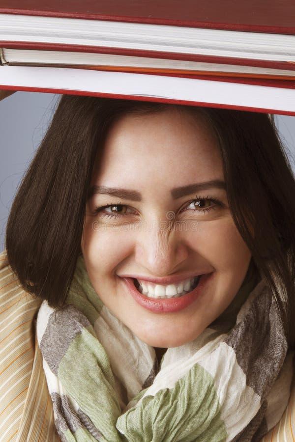 Jonge Student Girl Balancing Books op haar Hoofd & x28; Onderwijs en Se stock foto