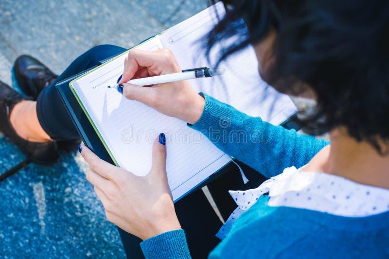 Jonge student met notitieboekje In openlucht online bestuderend concept stock foto's