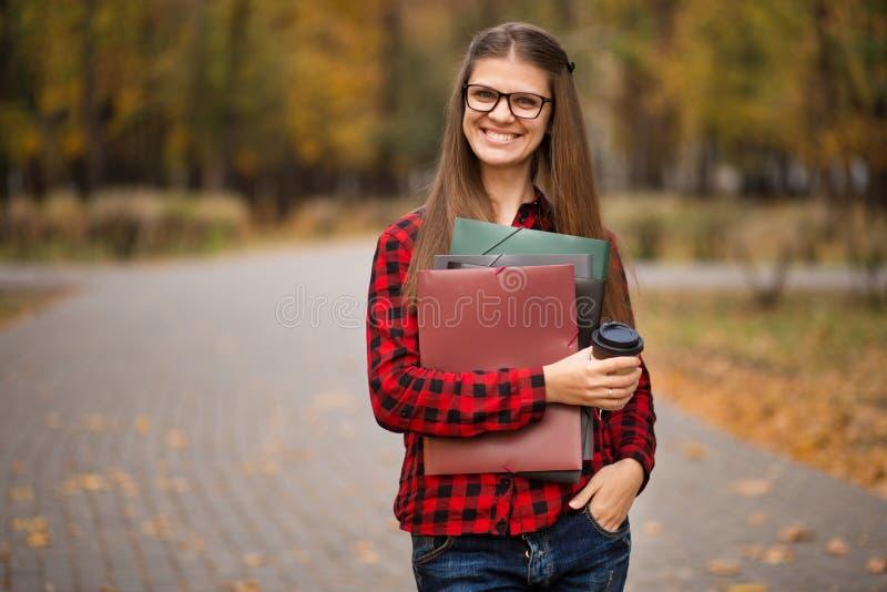 Jonge student in rood geruit overhemd met kop van koffie Portret van de mooie jonge omslagen van de vrouwenholding stock foto's
