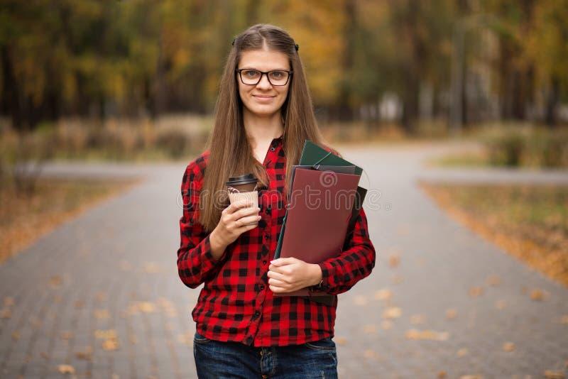 Jonge student in rood geruit overhemd met kop van koffie Portret van de mooie jonge omslagen van de vrouwenholding stock afbeeldingen