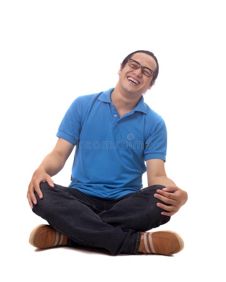 Jonge Student Sit bij Vloer en het Lachen stock afbeeldingen
