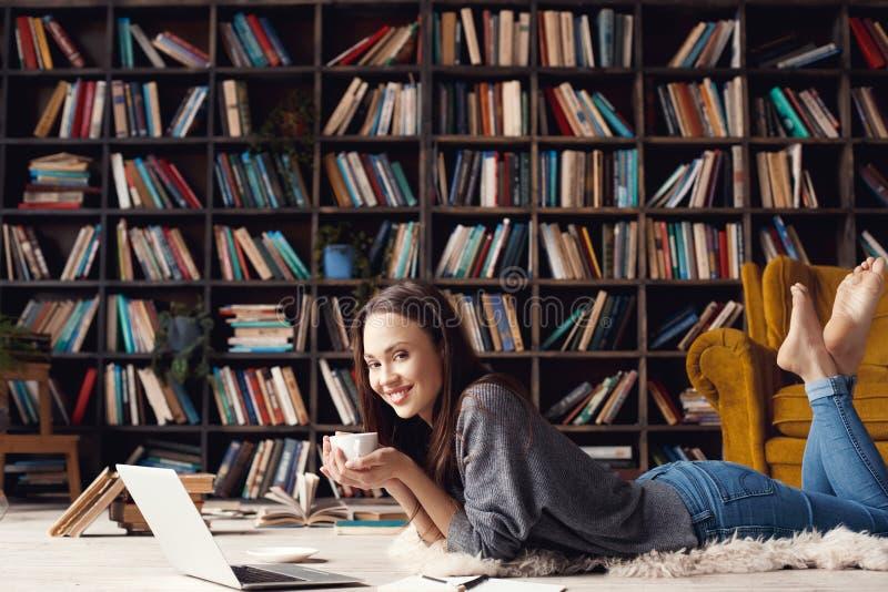 Jonge studente in bibliotheek thuis het liggen het drinken koffie stock afbeelding