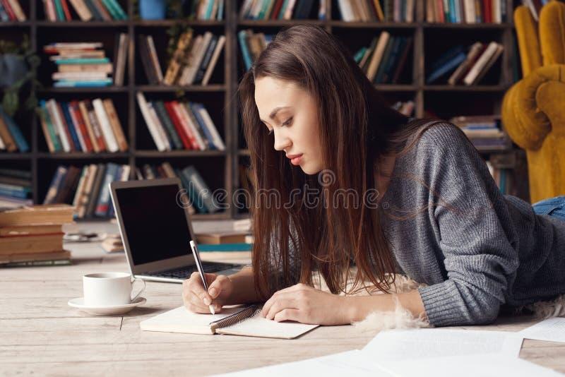 Jonge studente in bibliotheek thuis liggende het schrijven lezing stock foto