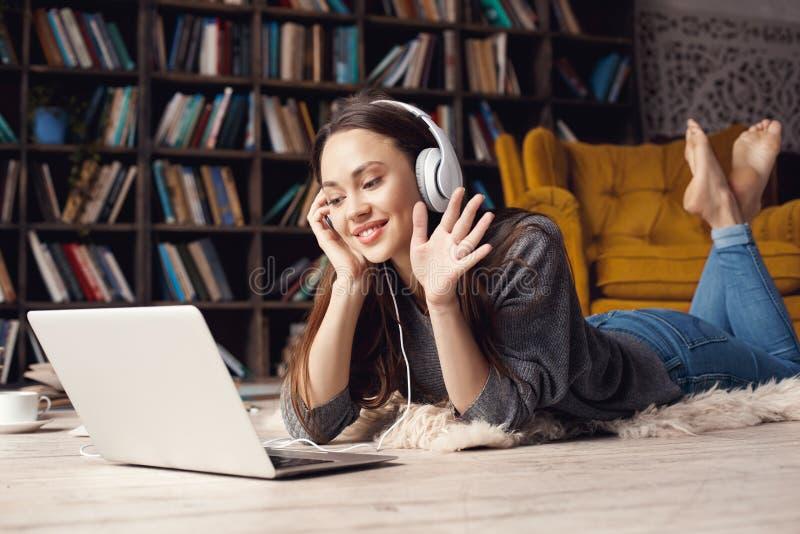 Jonge studente in bibliotheek thuis liggende videovraag stock afbeelding
