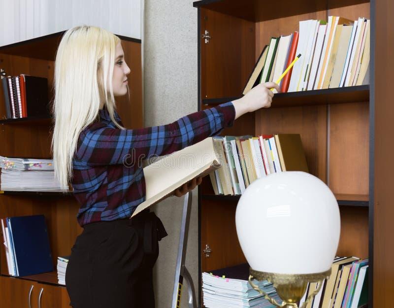 Jonge studente die en boek bevinden lezen zich dichtbij boekenrekken op bibliotheekachtergrond royalty-vrije stock foto