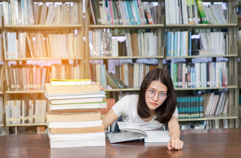Jonge Studente die met Glazen Ernstige boekoverlapping lezen stock fotografie